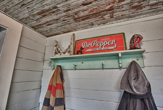 Living Vintage - Mudroom coat rack with old signs, corbels, and an antique dog