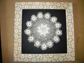 Antique doilies framed using reclaimed wallpaper