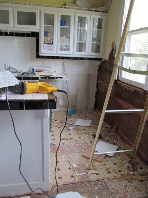 removing linoleum flooring to reveal old hardwood floors and the filth from removing the acoustical ceiling tiles