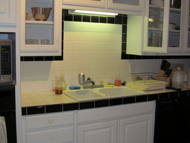 our kitchen before:  a sink facing a tile wall