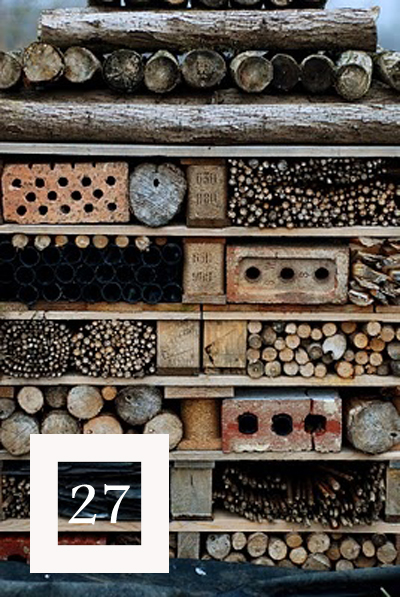 a bug hotel made with branches and small logs