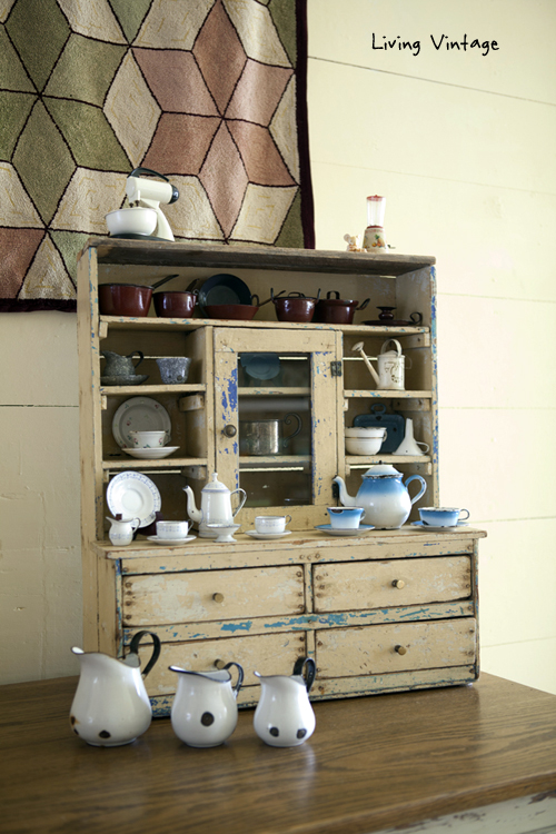 miniature enamelware in a cabinet and an antique rug - Living Vintage