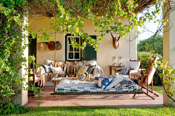 a wonderful porch with comfy seating and a hanging bed - Friday Favorites - Living Vintage