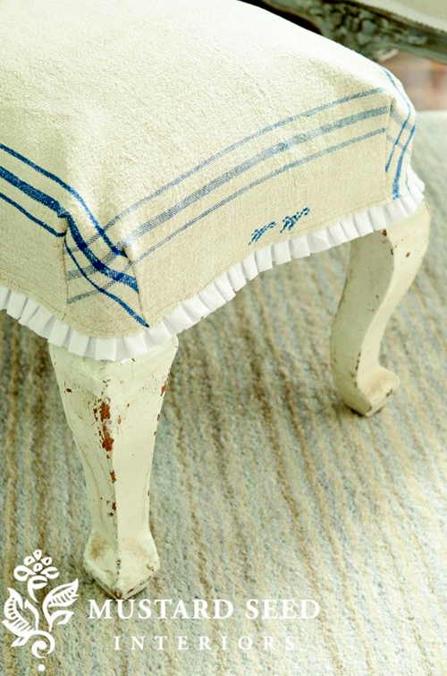 an ottoman slipcover made using a vintage tea towel