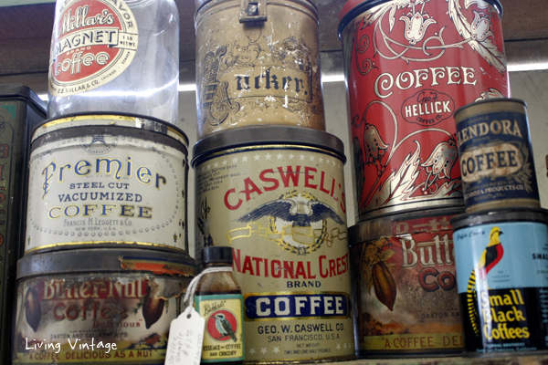 a collection of antique coffee tins and jars in Two Sisters Antiques booth