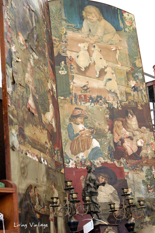 an old screen decoupaged with vintage illustrations of children and dogs