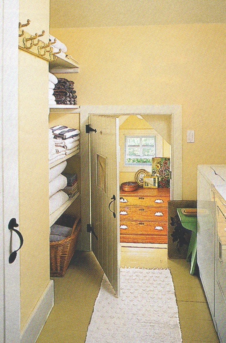 a small but very functional laundry room with linen storage nearby